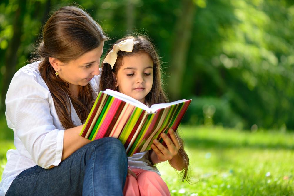 mom reading girl park